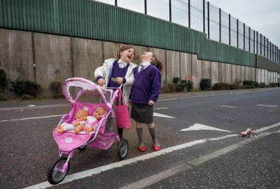 Weit weg von Brüssel. Hier: Noch immer trennt in West-Belfast eine Mauer, die höher ist als die Berliner Mauer es je war, die protestantischen von den katholischen Wohngebieten. Die beiden Mädchen mit ihren rotblonden Haaren haben die Schuluniform noch nicht abgelegt, als sie ihre beiden Puppen spazierenfahren. Die Mauer verhindert, dass sie den kleinen Puppenwagen auch durch die Straßen auf der protestantischen Seite schieben können. Belfast, Nordirland